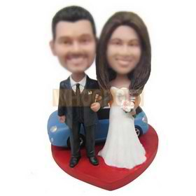 groom in black suit and bride in white wedding dress with their blue car custom bobbleheads