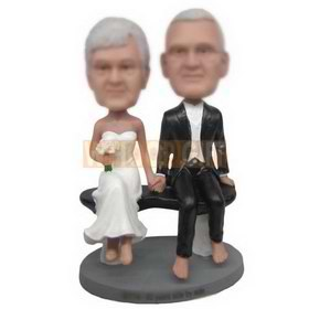 groom in black suit and bride in white wedding dress sitting on the chair custom bobbleheads