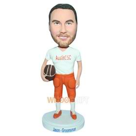 man in white T-shirt matching with orange pants handing football bobblehead