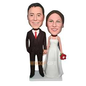 groom in black suit and bride in white wedding dress handing a flower bobblehead