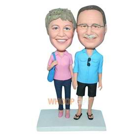 glasses husband in blue shirt and wife in pink shirt carrying a bag bobblehead