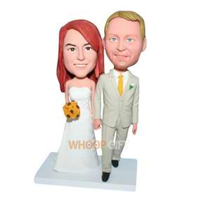groom in beige suit and bride in white wedding dress handing with a bunch of flowers bobblehead